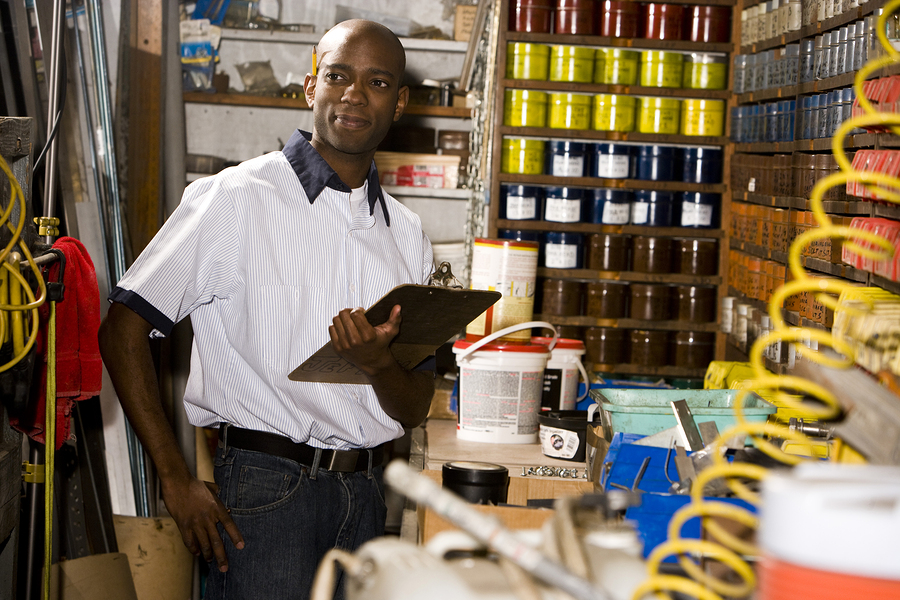 Portrait of African American worker holding a clipboard in printing company ** Note: Slight graininess, best at smaller sizes